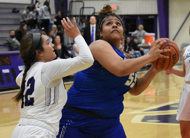 Kaliyah Montoya looks for room to get off her shot in the paint against Clovis defender Alandra Romero in the third quarter of Tuesday's District 4-5A game at Rock Staubus Gymnasium.