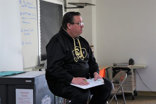 12th grade government teacher at Aztec High School, Joel Barton, listens to a student in his classroom at Aztec High School on Jan. 28, 2019.