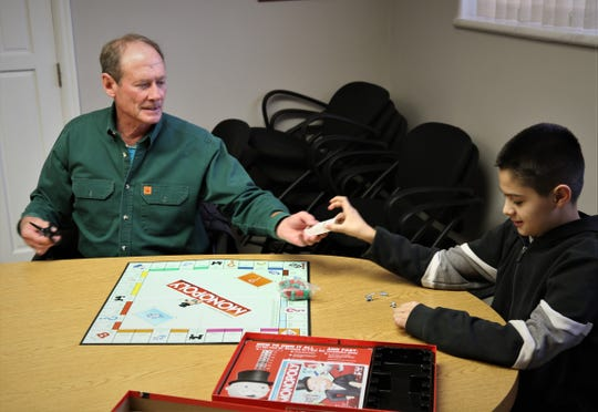 Dave Beavers, left, and Gabriel Gonzales prepare for a game of Monopoly on Jan. 28, 2020, at the offices of Big Brothers Big Sisters of San Juan County in Farmington.