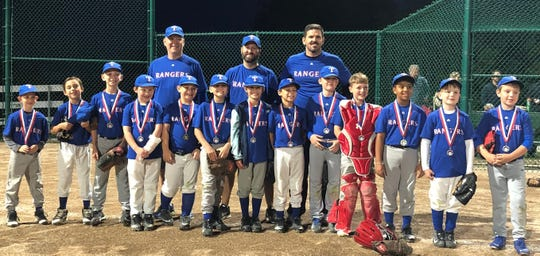 Coach David Sanders stands with his 9U baseball team after winning a medal.