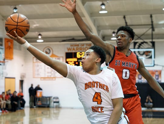 Brother Rice Warrior Xavier Thomas, left, snags a rebound.