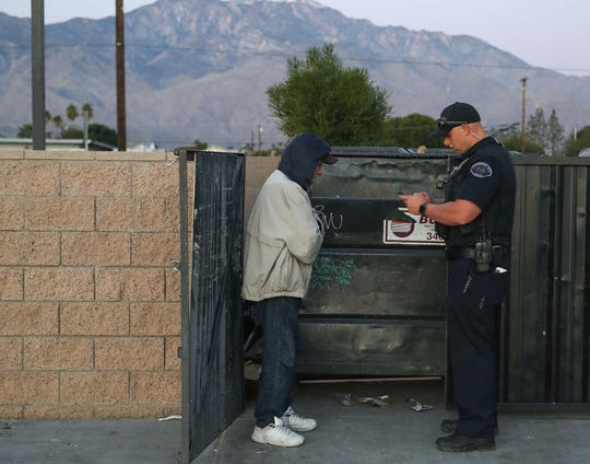 Cathedral City police officer Matt Buehler interviews Stefan Ballard during a count of the city's homeless.  Ballard had just spent the night inside the walls of the trash bin holding area, January 29, 2020.