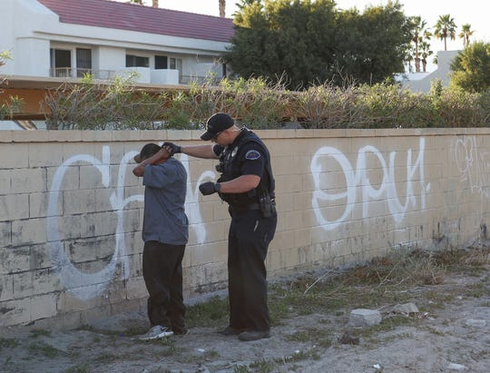 Cathedral City police officer Matt Buehler searches Jose Hernandez during a count of the city's homeless, January 29, 2020.