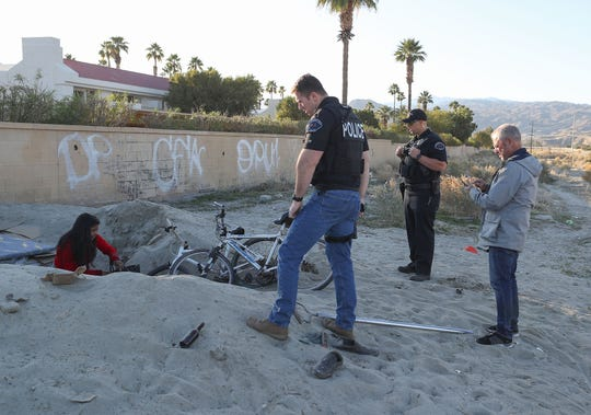 Cathedral City police officers Matt Buehler, Joe Brooks and volunteer Dave Boughner encounter three individuals inside of a large hole dug in the sand during a count of the city's homeless, January 29, 2020.