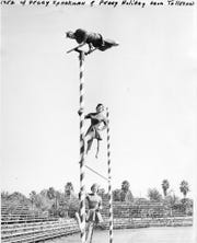 Dick Jacobs in the Sparky costume atop the goalpost at Arizona State with Peggy Sparkman and Peggy Holiday in 1952.