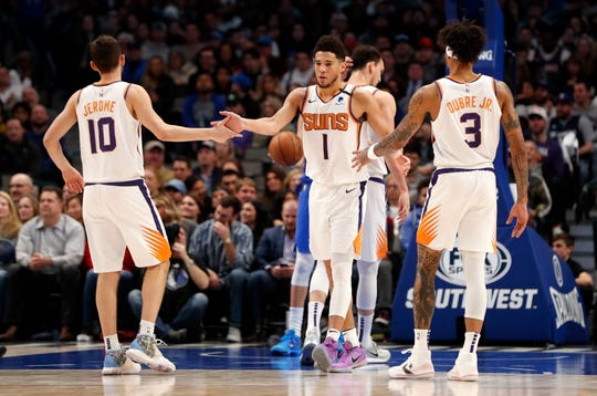 Jan 28, 2020; Dallas, Texas, USA;  Phoenix Suns guard Devin Booker (1) and  guard Ty Jerome (10) and forward Kelly Oubre Jr. (3) celebrate  during the third quarter against the Dallas Mavericks at American Airlines Center. Mandatory Credit: Kevin Jairaj-USA TODAY Sports