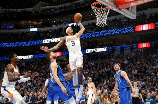 Phoenix Suns forward Kelly Oubre Jr. (3) goes for a slam dunk as Dallas Mavericks forward Maxi Kleber (42) and Dallas Mavericks guard Luka Doncic (77) look on during the first half of an NBA basketball game Tuesday, Jan. 28, 2020, in Dallas. (AP Photo/Ron Jenkins)