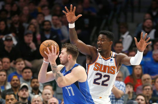 Dallas Mavericks guard Luka Doncic (77) looks to pass as Phoenix Suns center Deandre Ayton (22) defends during the first half of an NBA basketball game Tuesday, Jan. 28, 2020, in Dallas. (AP Photo/Ron Jenkins)