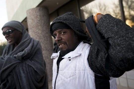 Lawrence Small (center) puts on his backpack and prepares to go to a shelter for food and showers with his partner (left) in Phoenix on Jan. 28, 2020. Small is currently homeless and living under a bridge in south Phoenix with his partner.