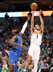 Phoenix Suns guard Devin Booker (1) shoots over Dallas Mavericks guard Tim Hardaway Jr. (11) during the first half of an NBA basketball game Tuesday, Jan. 28, 2020, in Dallas. Phoenix won 133-104. (AP Photo/Ron Jenkins)