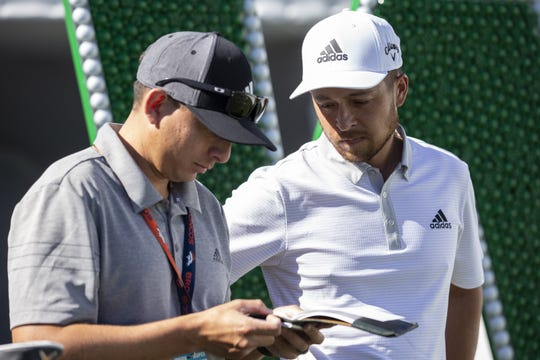 Xander Schauffele (right) talks with caddy Austin Kaiser before teeing off on the 17th tee during practice at the Waste Management Phoenix Open on Tuesday, Jan. 28, 2020, at TPC Scottsdale in Scottsdale, Ariz.