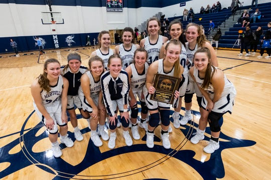 Marysville senior Gabby Fogarty poses with the rest of the team after they defeated L'anse Creuse 49-46 in overtime Tuesday, Jan. 28, 2020, at Marysville High School. During the game, Fogarty became the third girl to break 1,000 career points in the school's history.