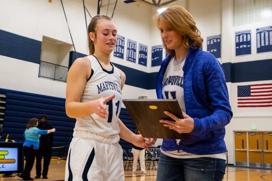 Brenda McLean, right, presents a plaque to Marysville senior Gabby Fogarty after breaking 1,000 career points during their game against L'anse Creuse Tuesday, Jan. 28, 2020, at Marysville High School. McLean, who graduated from Marysville in 1981, is one of the three girls who has broken 1,000 career points in the school's history.