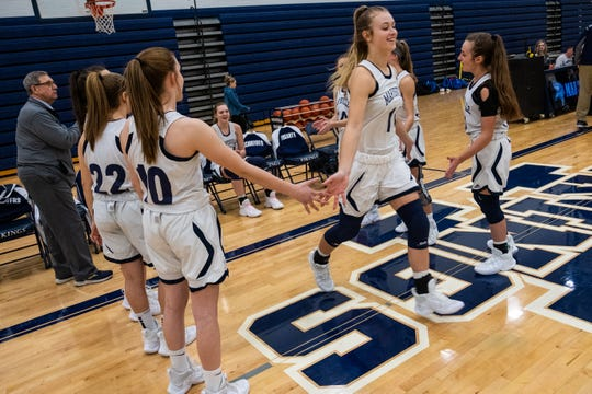 Marysville senior Gabby Fogarty (11) hi-fives her teammates before taking the court at the start of their game against L'anse Creuse High School Tuesday, Jan. 28, 2020, at Marysville High School. Fogarty became the third girl to score over 1,000 career points in the school's history during the game.