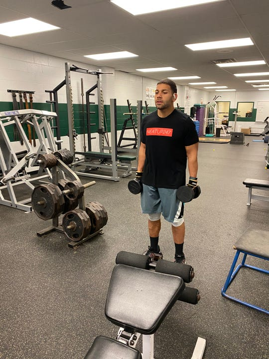 Clinton DeSouza is photographed working out in the Spackenkill High School gym. The football coach lost 80 pounds in a year and plans to host a weight loss seminar.