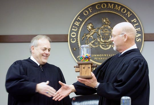 In this file photo from Jan. 3, 2011, Common Pleas Judge Richard K. Renn, right, presents incoming President Judge Stephen P. Linebaugh with an M&M dispenser after a swearing-in ceremony. Renn, 68, is retiring on Friday after serving for more than 22 years on the York County Court of Common Pleas.