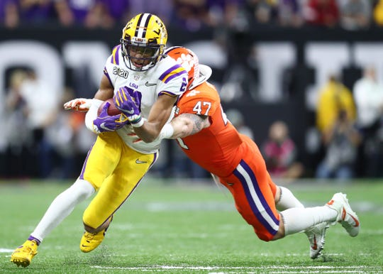 LSU wide receiver Justin Jefferson is tackled by Clemson Tigers linebacker James Skalski. Jefferson caught nine passes for 106 yards against Clemson in the national championship game.