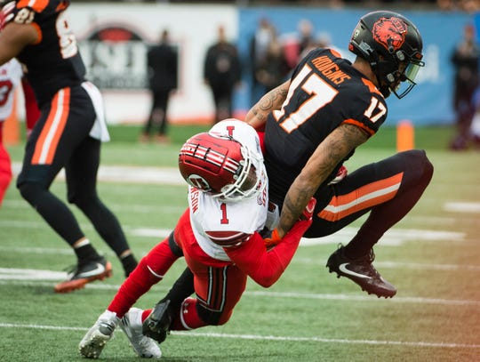 Oregon State wide receiver Isaiah Hodgins is tackled on a pass play by Utah defensive back Jaylon Johnson.