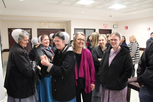 Elizabeth Catlin, center, in pink sweater, is surrounded by supporters outside the Yates County Courtroom following her Jan. 28 arraignment on 95 felony charges.