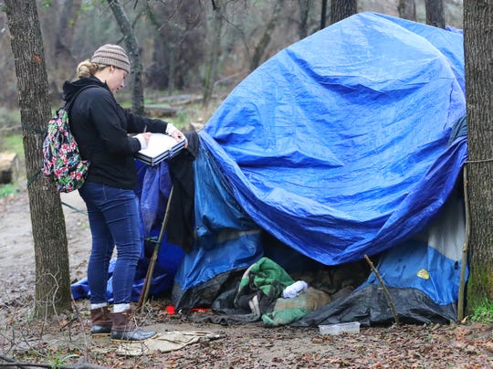 Volunteer Jade O'Dell poses questions to a person in a tent at the Henderson Open Space during the annual Point in Time homeless survey in Redding on Tuesday, Jan. 28, 2020.