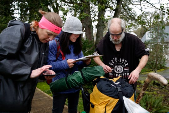 Michael O'Sullivan, 58, is interviewed by volunteers Gretchen Bennett, left, and Eunice Kim, with the city of Salem, during the Point-in-Time count in downtown Salem on Jan. 29, 2020. The annual survey of people experiencing homelessness has been expanded to last a week this year.