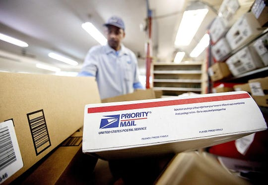 Packages wait to be sorted in a Post Office as U.S. Postal Service letter carrier Michael McDonald, gathers mail to load into his truck before making his delivery run, in Atlanta. The USPS raised the prices of domestic Priority Mail packages, effective Jan. 26.