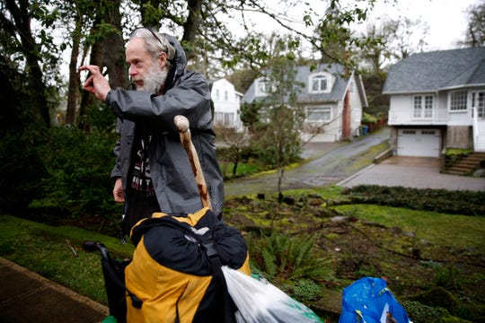 Michael O'Sullivan, 58, gives an OK gesture to a volunteer who gave him her rain coat during the Point-in-Time count in downtown Salem on Jan. 29, 2020. The annual survey of people experiencing homelessness has been expanded to last a week this year.