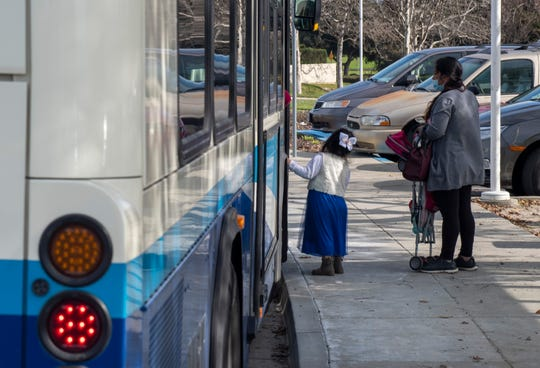 A young girl stands next to another woman who is wearing a face mask as they both wait to get inside the bus on Jan. 29, 2020.