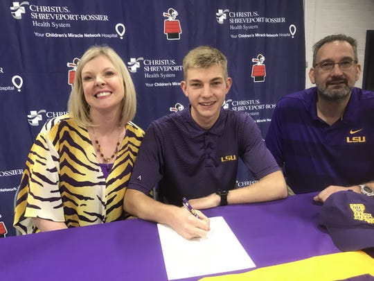Flanked by his parents, Loyola distance runner Will Dart signed with LSU on Wednesday.