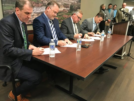 Avera Medical Group President Dave Flicek, Sanford Health President Paul Hanson, Minnehaha County Commissioner Dean Karsky and Sioux Falls Mayor Paul TenHaken sign the bylaws for the Community Triage Center Board during a signing ceremony Wednesday morning.