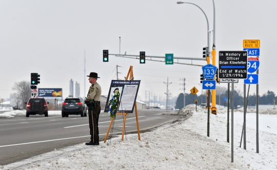 Stearns County Sheriff's Office honor guard member Brian Theisen stands watch Wednesday, Jan. 29, 2020, near a wreath and memorial placed at the location where officer Brian Klinefelter was killed 24 years ago in St. Joseph. Honor guard members stood watch at the location for one hour following the noon ceremony Wednesday.