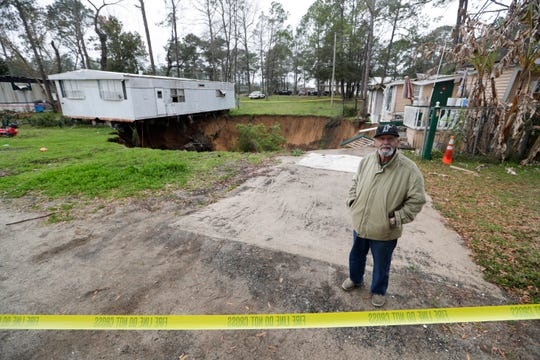 Anwar El Khouri, 74, stands in front of the 50-foot and growing sinkhole that threatens his mobile home and another in the Capital Circle Pines trailer park Wednesday, Jan. 29, 2020.