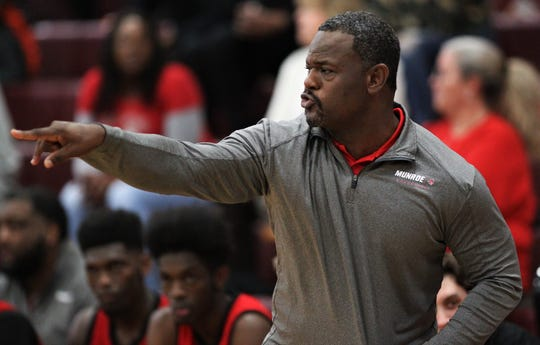 First-year Munroe head coach Dimitric Salters talks to his players on the court as Madison County's boys basketball team beat Munroe 59-54 in overtime on Jan. 28, 2020.