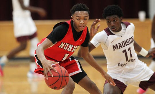 Munroe junior Jaquez Price tries to spin away from a half-court trap as Madison County's boys basketball team beat Munroe 59-54 in overtime on Jan. 28, 2020.
