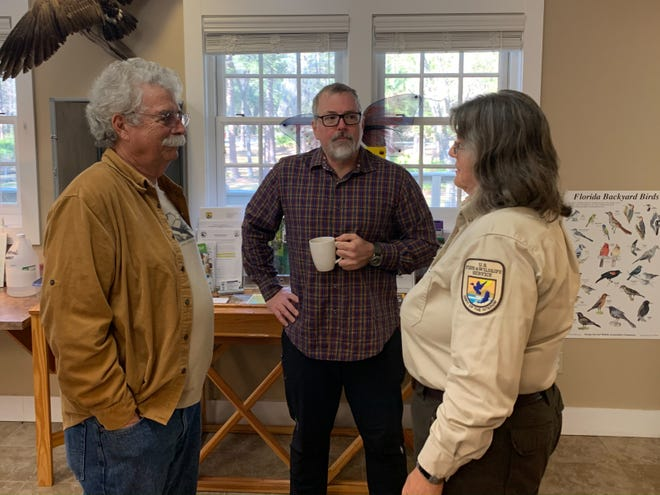 """Board member Bill Clutter, left, with """"Annhilation"""" author  Jeff VanderMeer, center, who presented a check for $5,000 to Friends of the St. Marks National Wildlife Refuge, and and Terry Peacock, right, on Jan. 21."""