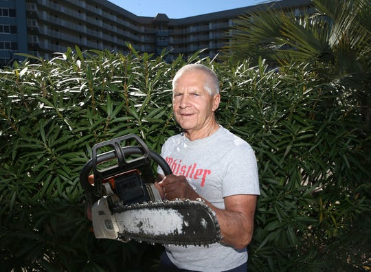 Gary Fitzgerald pictured with his chainsaw in front of the condominium complex in Panama City Beach where he stays during the winter.