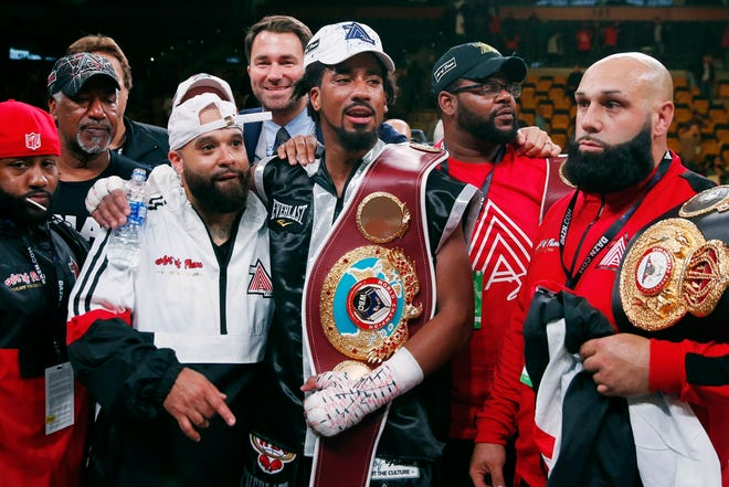 In this Oct. 21, 2018, file photo, Demetrius Andrade, center, stands with members of his team after defeating Walter Kautondokwa in a WBO middleweight championship boxing match in Boston.