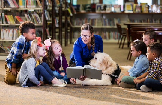 Children are read a story in a library.