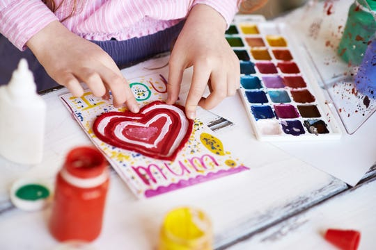 Little girl painting a Valentine card