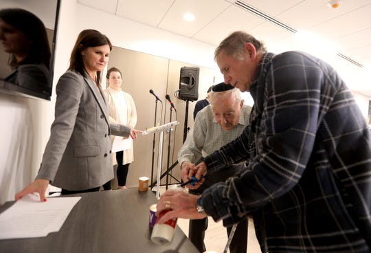 Mike Hussar of Monsey helps Holocaust survivor Joseph Bienstock, 99, of Monsey, light a candle during an event commemorating International Holocaust Remembrance Day and the 75th anniversary of the liberation of Auschwitz at the Holocaust Museum & Center for Tolerance and Education, located at Rockland Community College in Ramapo Jan. 27, 2020. At left is Andrea Winograd, Executive Director of the museum. The museum was reopening after a multi-year renovation.