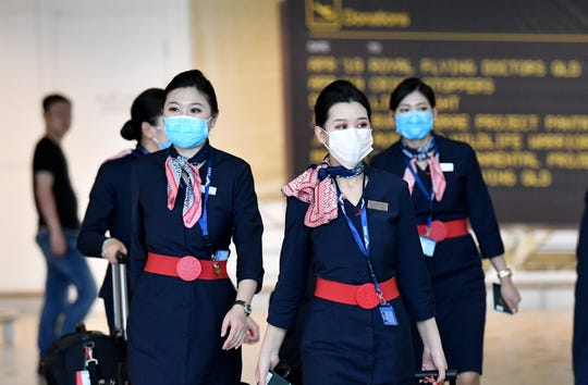 Cabin crew members from China Eastern Airlines wearing protective face masks make their way through Brisbane International Airport in Brisbane, Australia. The Trump administration is considering a ban on flights between the U.S. and China.