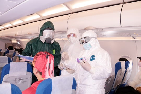 Police and medical personnel take temperature tests of passengers on board an airplane at the airport in Zhoushan City, Zhejiang Province, China on Jan. 28, 2020.