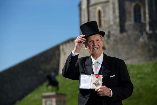 British radio and television presenter Nicholas Parsons poses with his Commander of the Order of the British Empire medal given to him by Queen Elizabeth II at an Investiture ceremony at Windsor Castle April 15, 2014.
