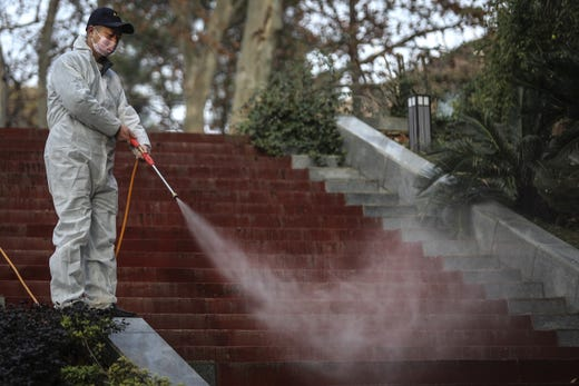 A man uses alcohol to disinfect the grounds nearby the Wuhan Huoshenshan hospital construction site on Jan. 28, 2020 in Wuhan,  China.