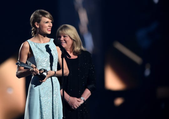 Taylor Swift (left) accepts the Milestone Award from mother Andrea Swift at the 2015 Academy of Country Music Awards. Her mom's cancer battle gave Swift a new perspective.
