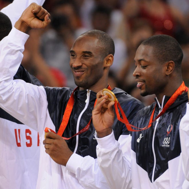 Kobe Bryant pumps his fist and Dwyane Wade looks at his gold medal after the USA beat Spain 118-107 in the men's basketball gold medal game in the 2008 Beijing Olympics.