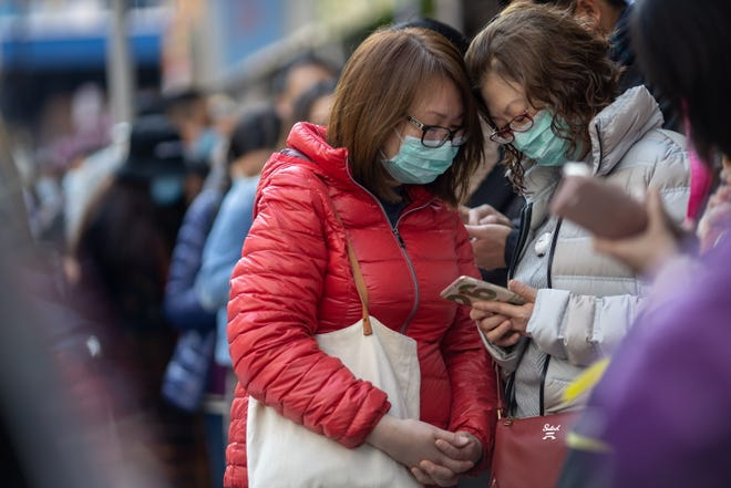 People line up to receive free face masks to protect themselves against the Wuhan coronavirus at a pharmacy in Tsuen Wan, Hong Kong, China on Jan. 28, 2020.