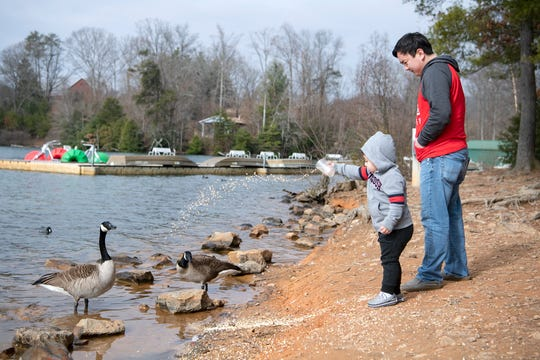 Buncombe County Parks such as Lake Julian have not been in full operation because of the COVID-19 pandemic, and that impacted when bathrooms were open. In this file photo, Finn Hilgeman, 2, and his dad, Spencer, toss feed to a pair of geese at Lake Julian Park on Jan. 30, 2020.