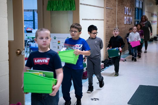 Students at Pennfield's Purdy Elementary School carry books to read in the hallway on Wednesday, Jan. 29, 2020 in Battle Creek, Mich. The district is considering a $22 million bond to improve facilities.