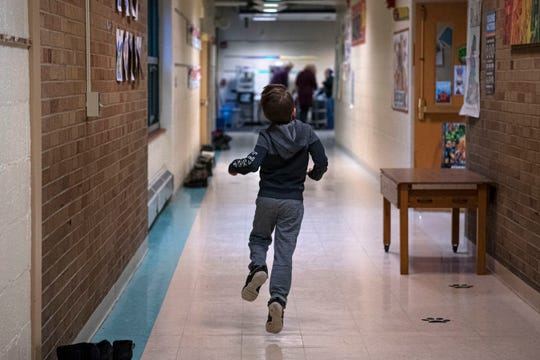 A child skips down the halls of Pennfield's Purdy Elementary School on Wednesday, Jan. 29, 2020 in Battle Creek, Mich. The district is considering a $22 million bond to improve facilities.